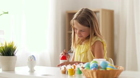 nisan : happy girl coloring easter eggs at home Stok Video