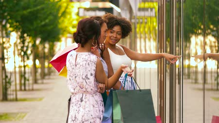 south african : women with shopping bags looking at shop window