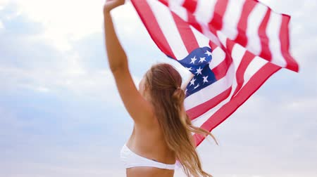 raised : happy young woman with american flag on beach