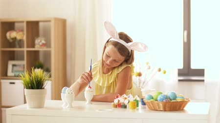 saç bantı : happy girl coloring easter eggs at home Stok Video
