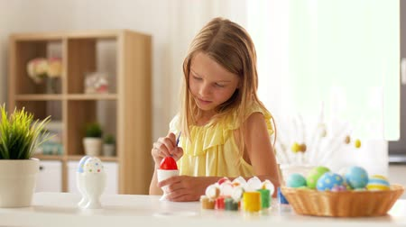 kwiecień : happy girl coloring easter eggs at home Wideo