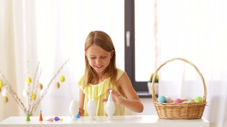 крошечный : happy girl decorating easter eggs at home