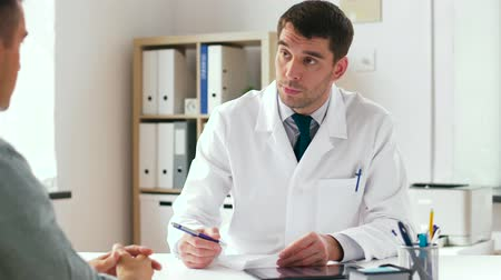referral : doctor writing prescription for patient at clinic Stock Footage