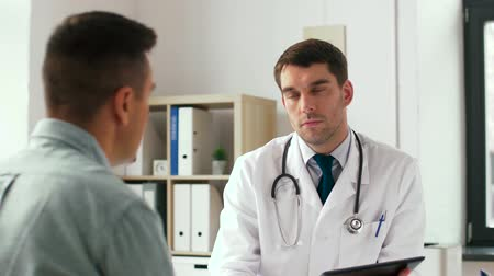 gyógyász : doctor with tablet pc and male patient at hospital