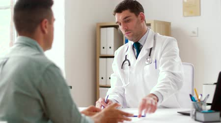 referral : doctor giving prescription for patient at clinic