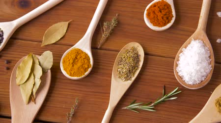 tempero : spoons with different spices on wooden table Vídeos