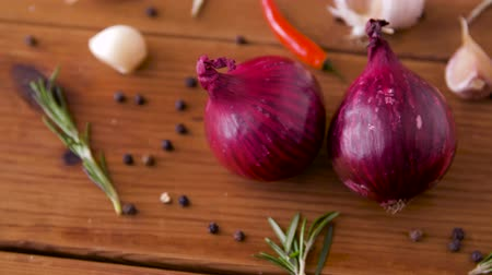 natural spicy : onion, garlic, chili pepper and rosemary on table Stock Footage