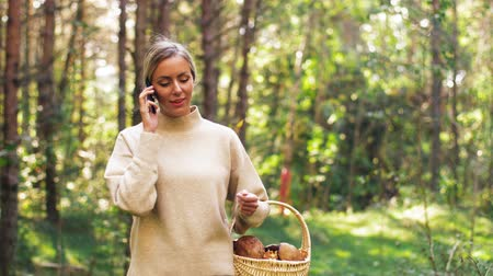borowik : woman with mushrooms calling on cellphone in woods