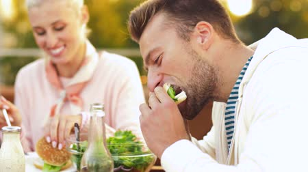 cidra : man with friends eating burger at rooftop party