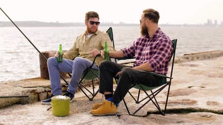 fisher : happy friends fishing and drinking beer on pier Stock Footage