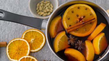 mulled wine : pot with hot mulled wine, orange slices and spices