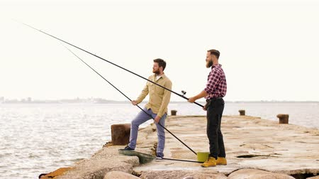 fisher : happy friends with fishing rods on pier Stock Footage