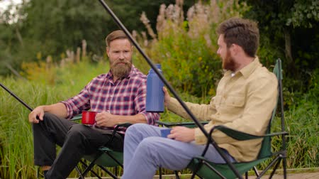 fisher : friends fishing and drinking tea from vacuum flask