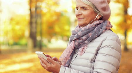old radio : old woman with smartphone and earphones in autumn
