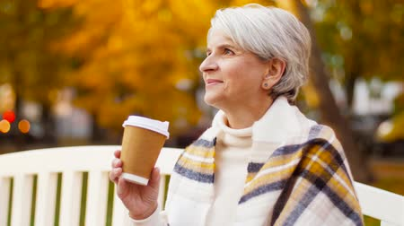 навынос : senior woman drinking coffee in autumn park