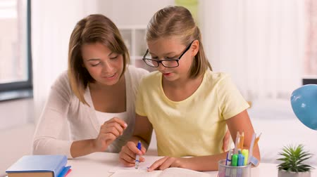 préadolescent : mother and daughter doing homework together