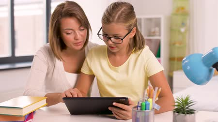 özel öğretmen : mother and daughter with tablet pc doing homework Stok Video