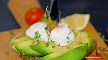 poached egg : knife cutting toast with pouched egg and avocado