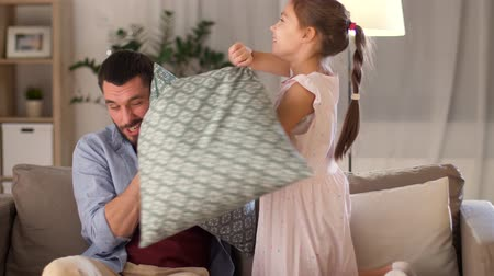 pre hispanic : father and daughter having pillow fight at home