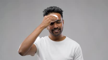 toner : smiling indian man cleaning face with cotton pad