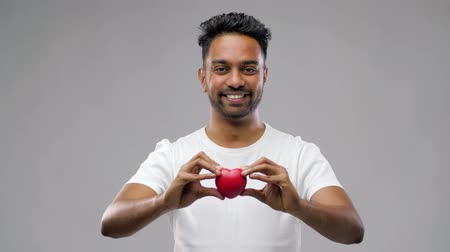 благотворительность : indian man with red heart over grey background