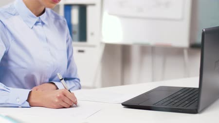 bookkeeping : businesswoman with laptop and papers at office