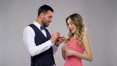 nişanlısı : happy man giving engagement ring to woman