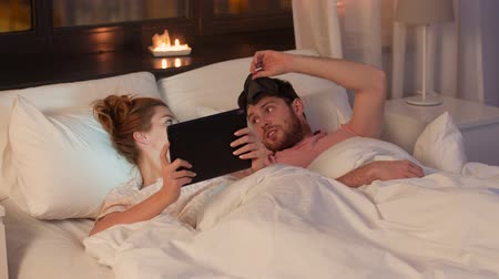 bezsennosć : woman using tablet pc and disturbed man awaking