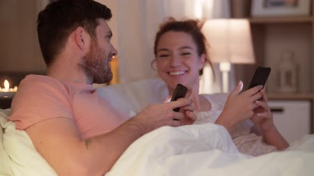 yatma zamanı : happy couple using smartphones in bed at night Stok Video