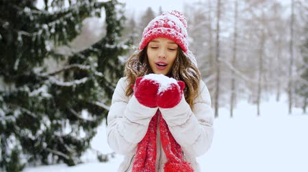 subúrbio : happy young woman blowing to snow in winter forest