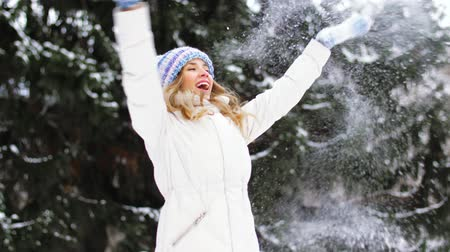 x mas : happy young woman throwing snow in winter forest