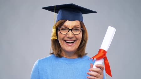 mortarboard : happy senior graduate student woman with diploma