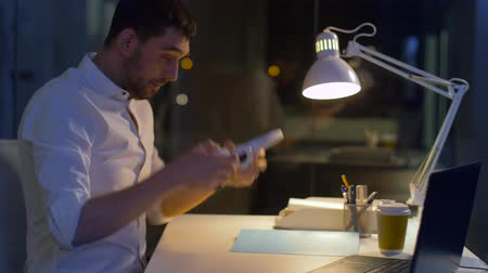 dinleme : businessman with laptop and headphones at night Stok Video
