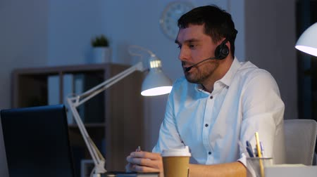 телефон доверия : businessman in headset with laptop at night office Стоковые видеозаписи
