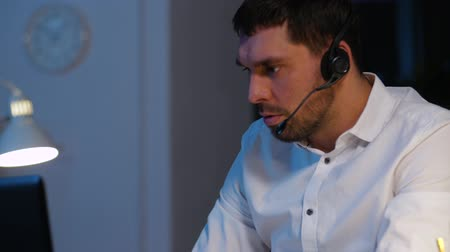 телефон доверия : businessman in headset with coffee at night office Стоковые видеозаписи