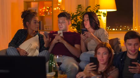 ближневосточный : friends with smartphone watching tv at home