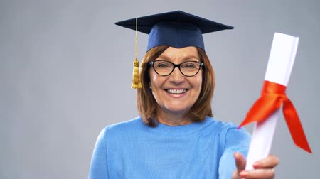 grãos : happy senior graduate student woman with diploma