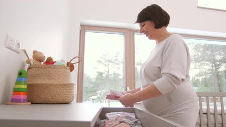 drawer : happy pregnant woman setting baby clothes at home Stock Footage