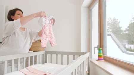 cradle : happy pregnant woman setting baby clothes at home Stock Footage