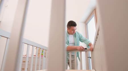 paternal : father with screwdriver assembling baby bed Stock Footage