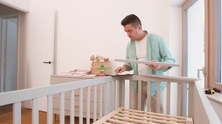 szopka : father with tablet pc assembling baby bed at home