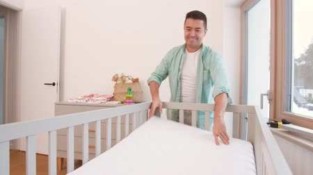paternal : father arranging baby bed with mattress at home Stock Footage