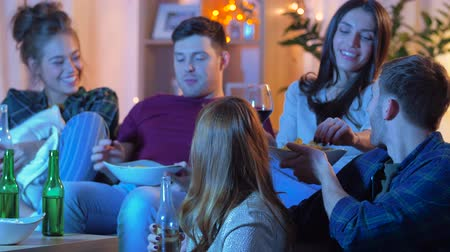 bottle feeding : friends with drinks and snacks watching tv at home Stock Footage
