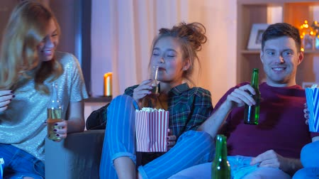 cidra : friends with beer and popcorn watching tv at home