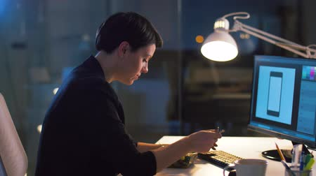 editor : businesswoman with computer eating at night office Stock Footage