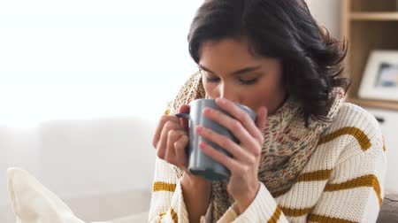 baca : sick young woman in scarf drinking hot tea at home