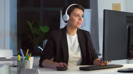 playlist : businesswoman in earphones with computer at office