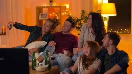 alkoholos : friends with smartphone watching tv at home