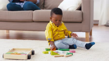 develop : african american baby boy playing with toy blocks