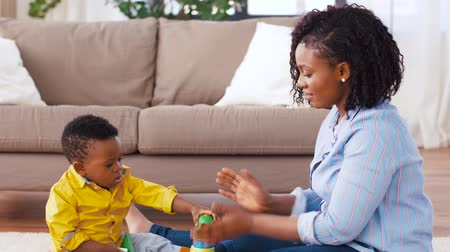 babysitter : mother and baby playing with toy blocks at home